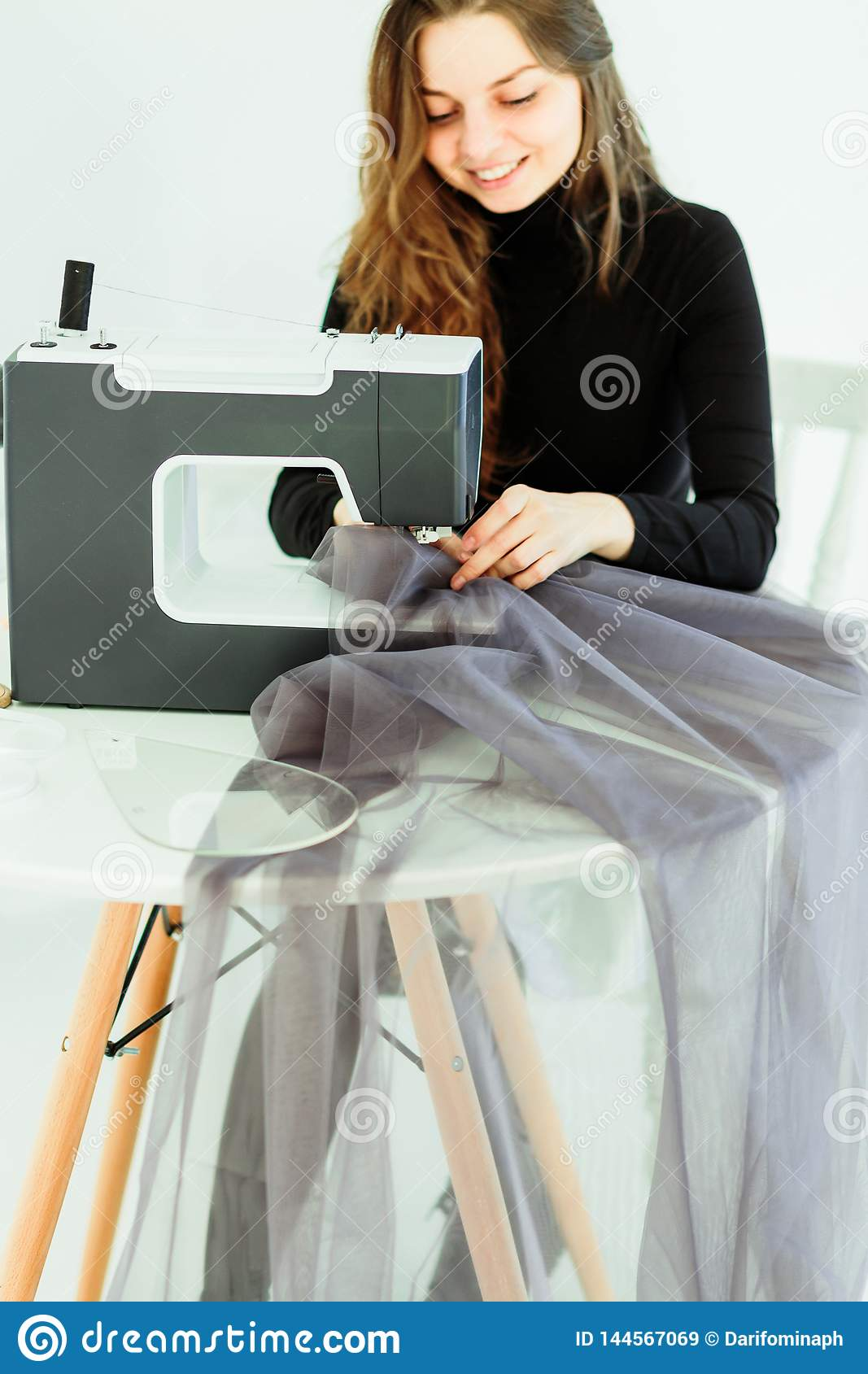 Young dressmaker woman sews clothes on sewing machine