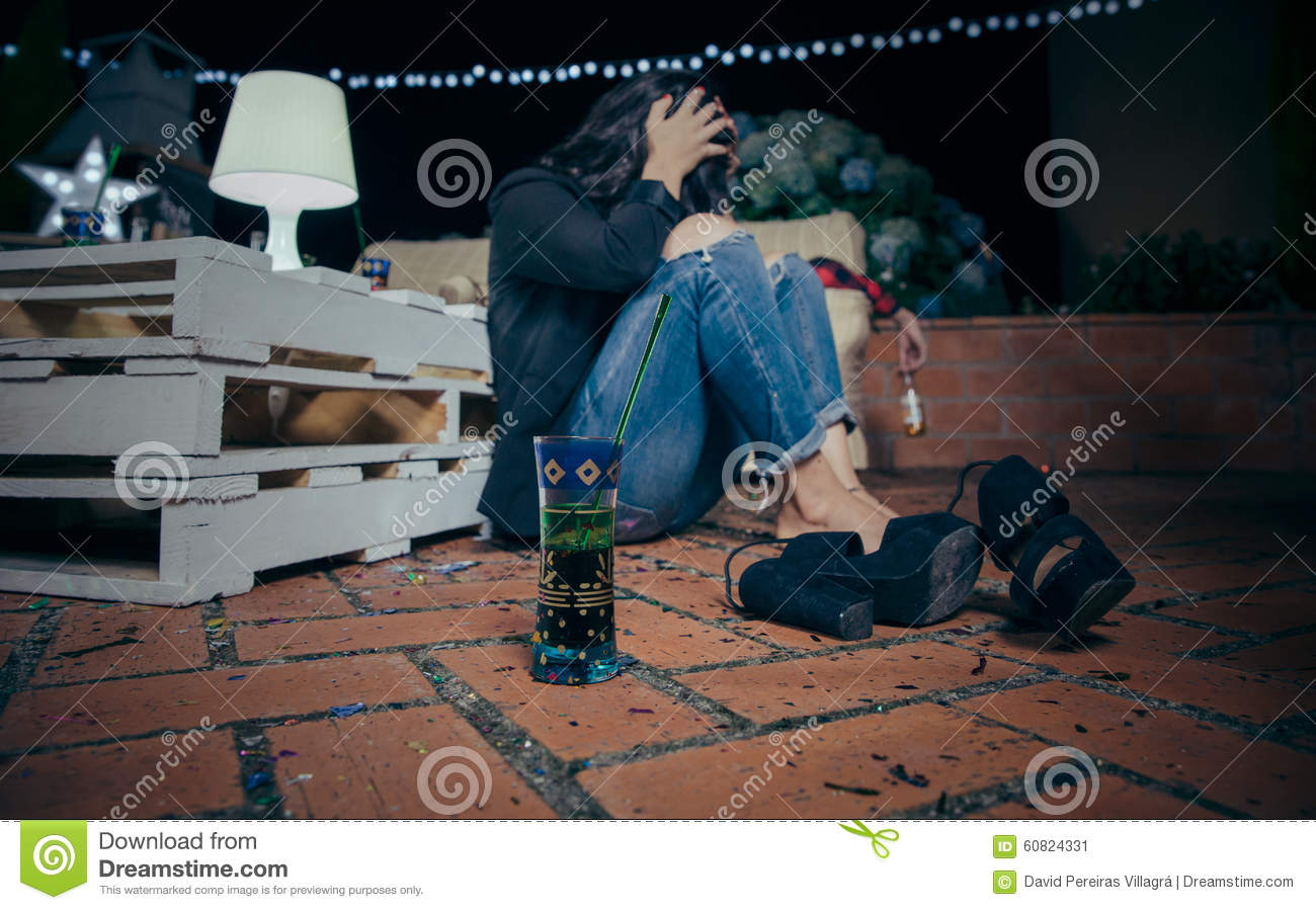 Young drunk woman sitting in the floor after party