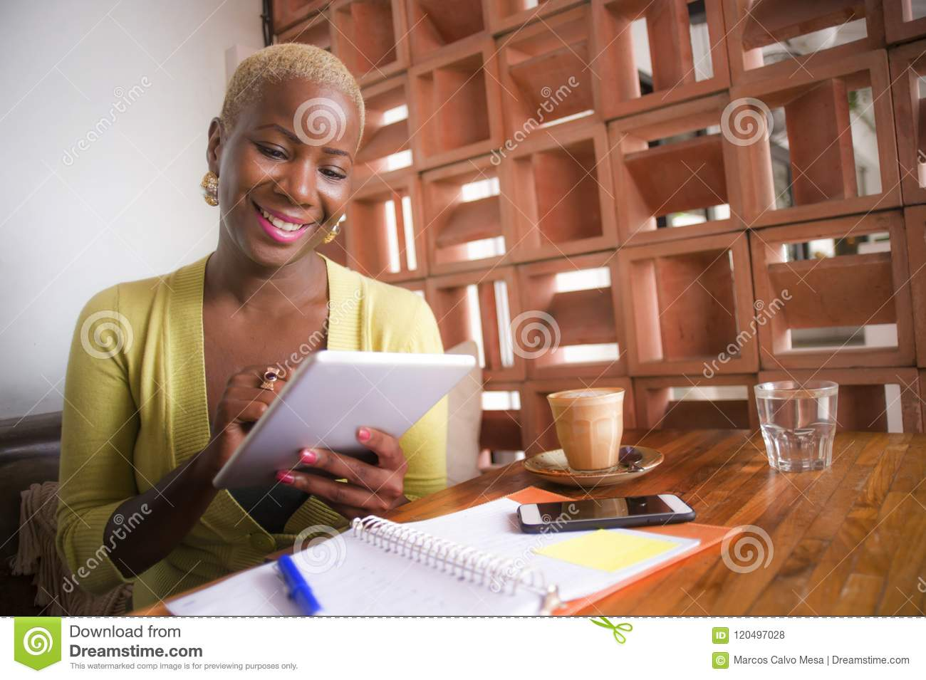 Young elegant and beautiful black African American business woman working online with digital tablet pad at coffee shop smiling ha