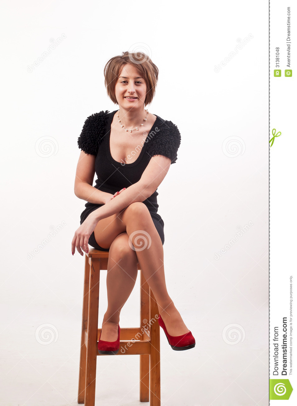 Young Elegant Woman In Black Dress Sitting On Chair
