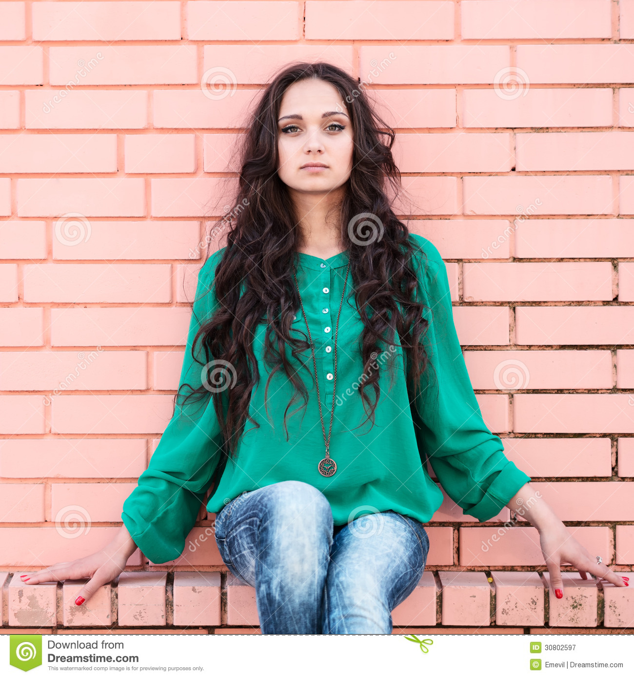 Young elegant woman on a brick wall backround