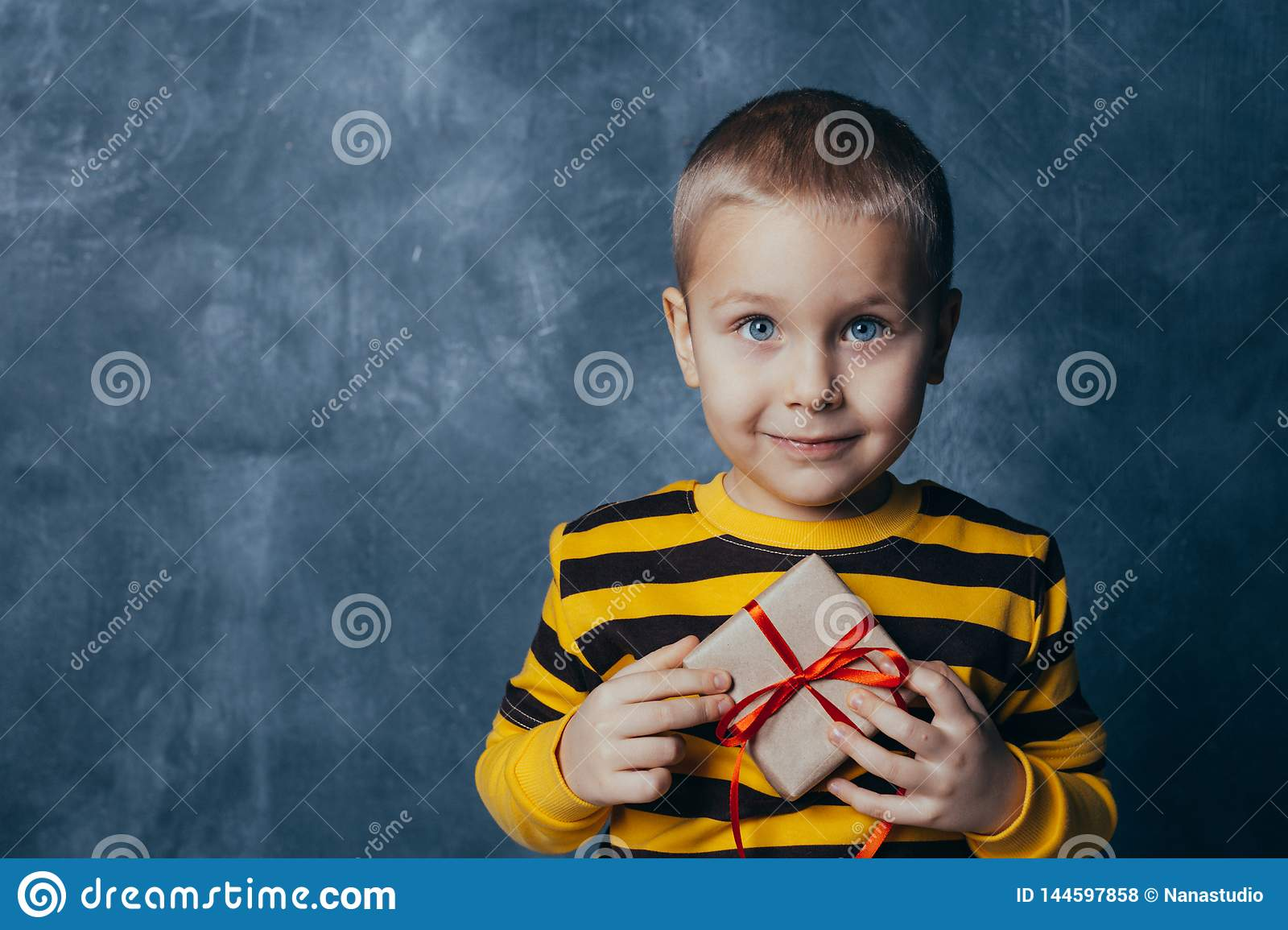 A young emotional boy holds in his hands a gift with a red bow standing on a blue studio background