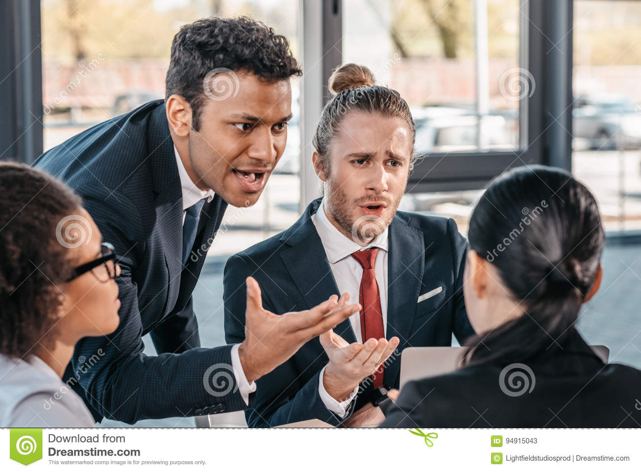 Young emotional businesspeople in formalwear arguing at meeting in office