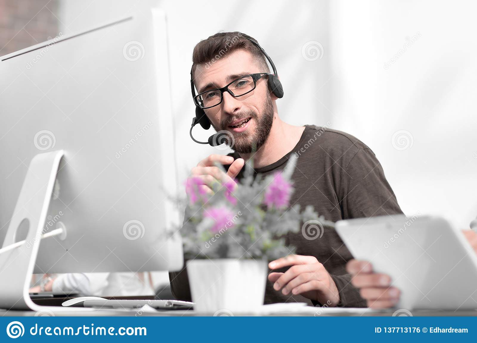 Young employee in the headset sitting at a table in the business cente