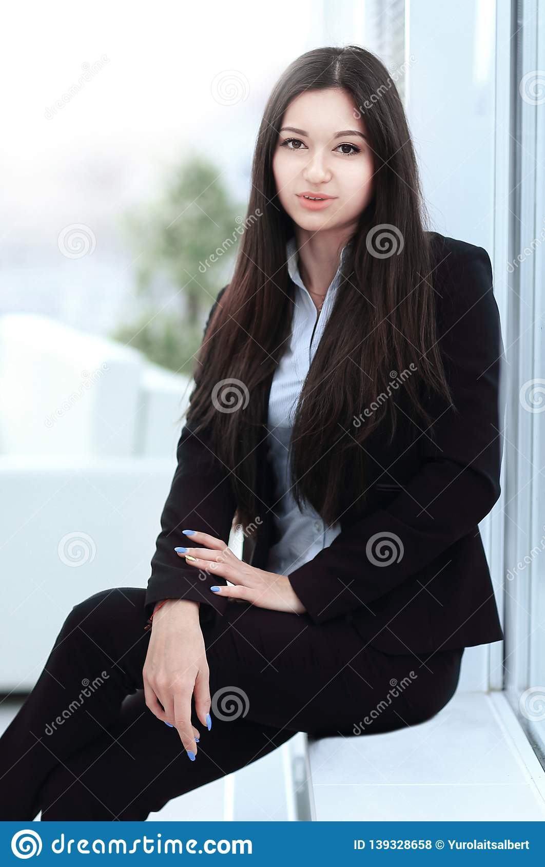 Young employee sitting near a window in the office