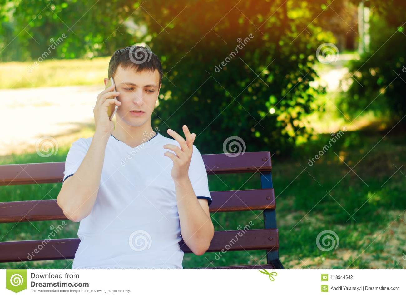 A young European guy in a white T-shirt speaks on the phone and sits on a bench in the city park and points with your finger. The