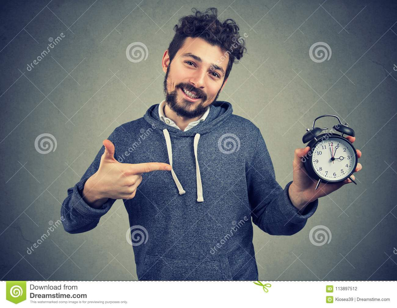 Young expressive happy hipster man holding alarm clock