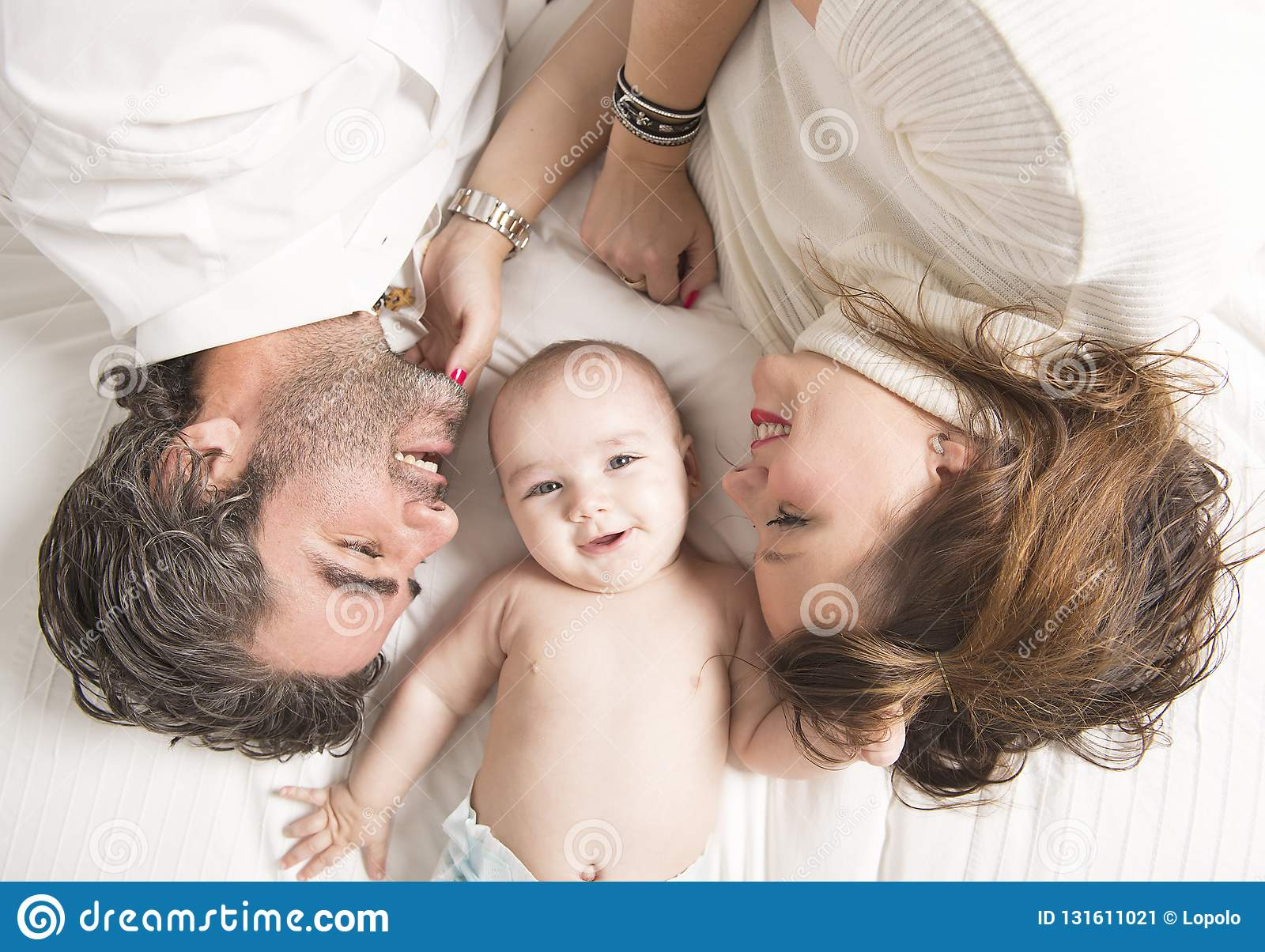 A young family with baby on bed view from above