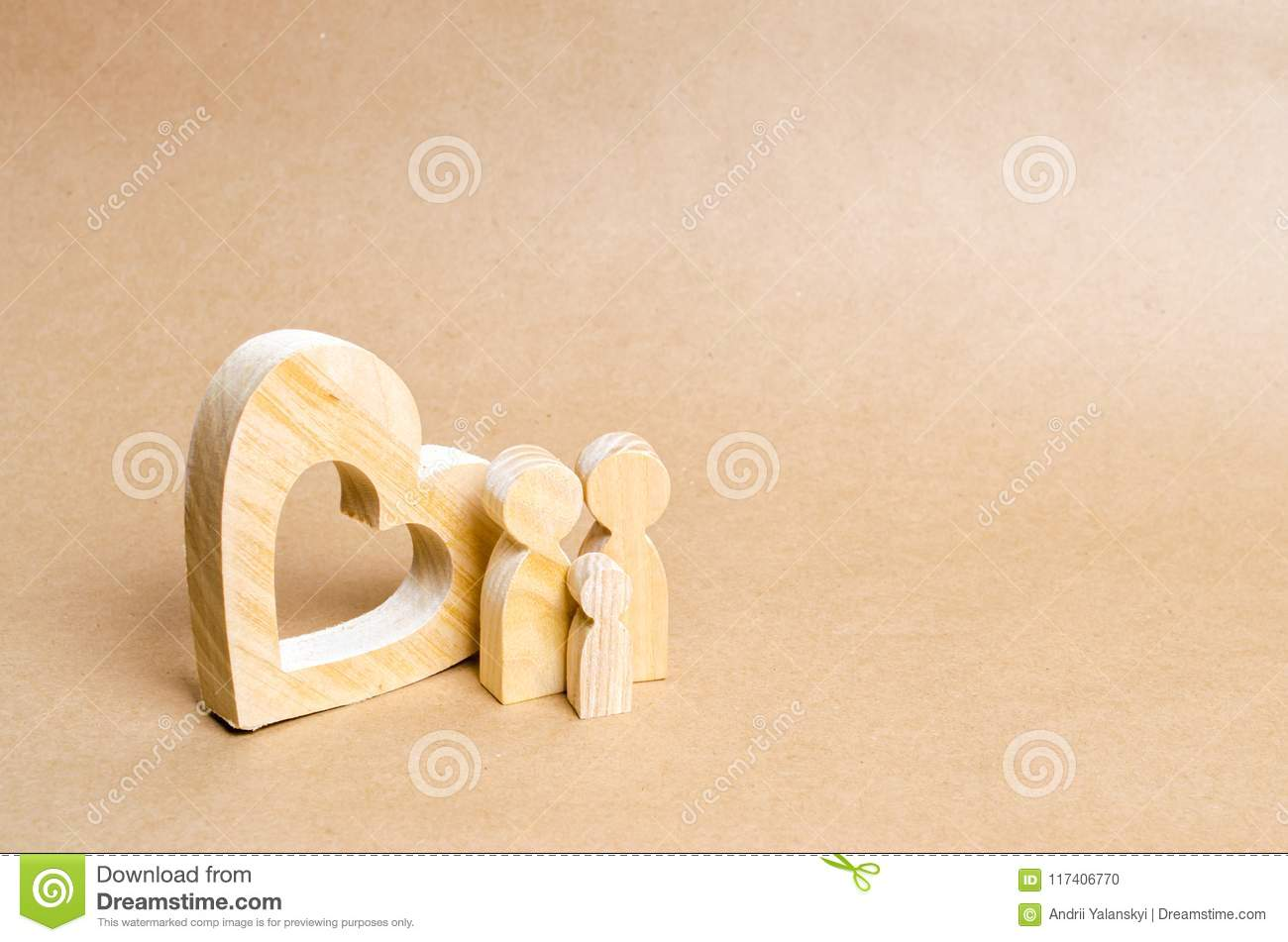 A young family with a child is standing near a wooden heart. Love and loyalty, a strong young family. Family relationships.