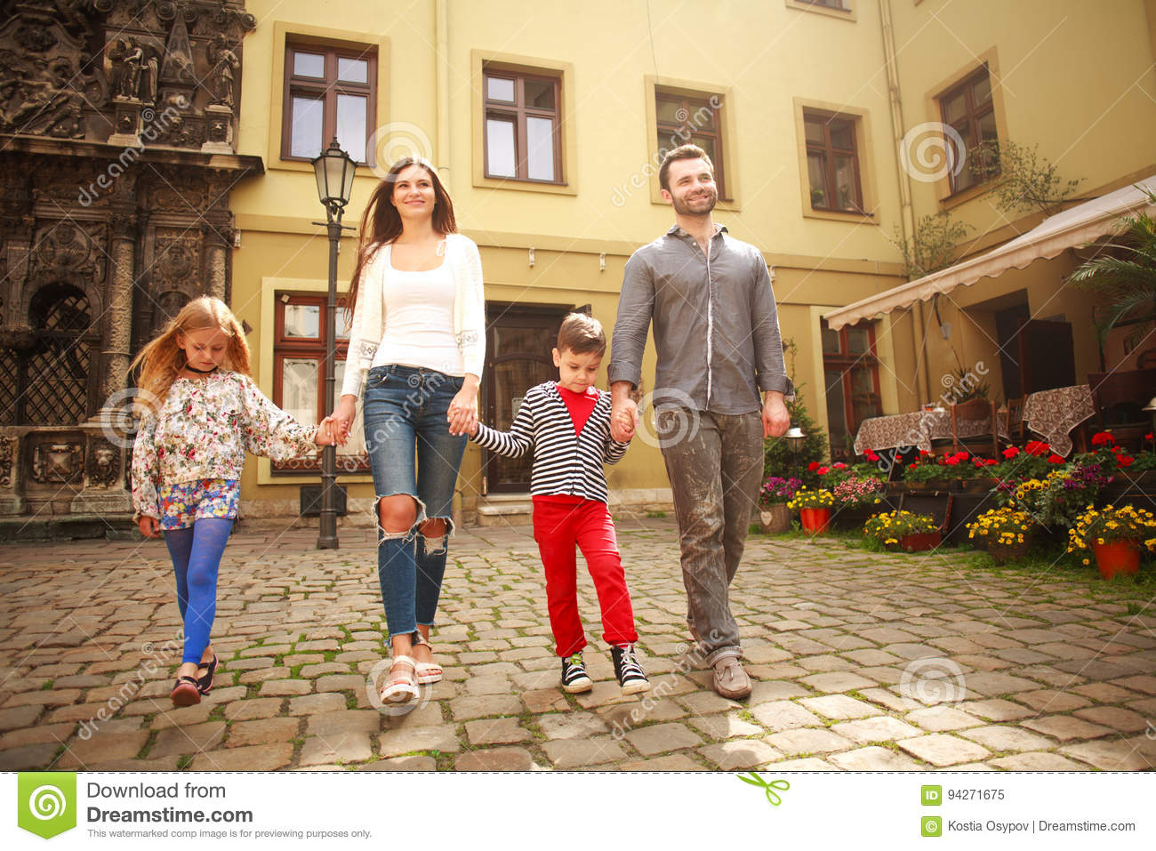 Young family with children on walk the street of tourist city