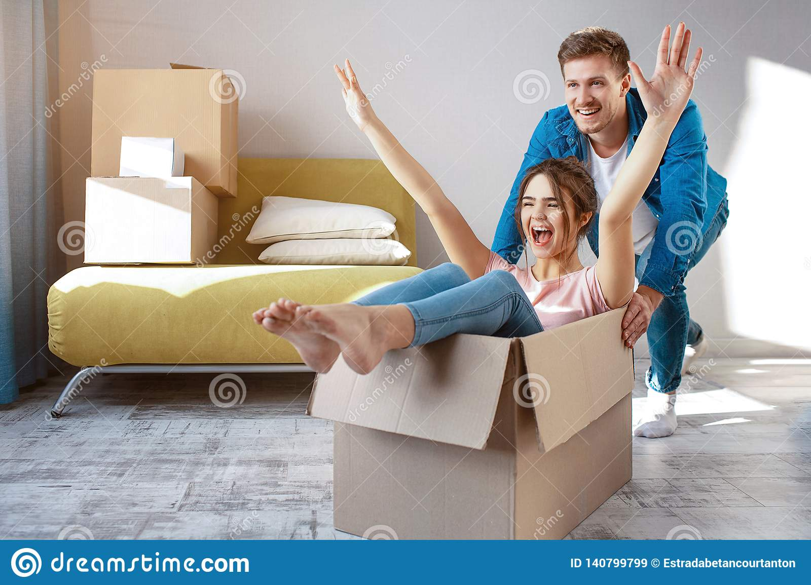 Young family couple bought or rented their first small apartment. Cheerful happy people having fun. She sit in box and
