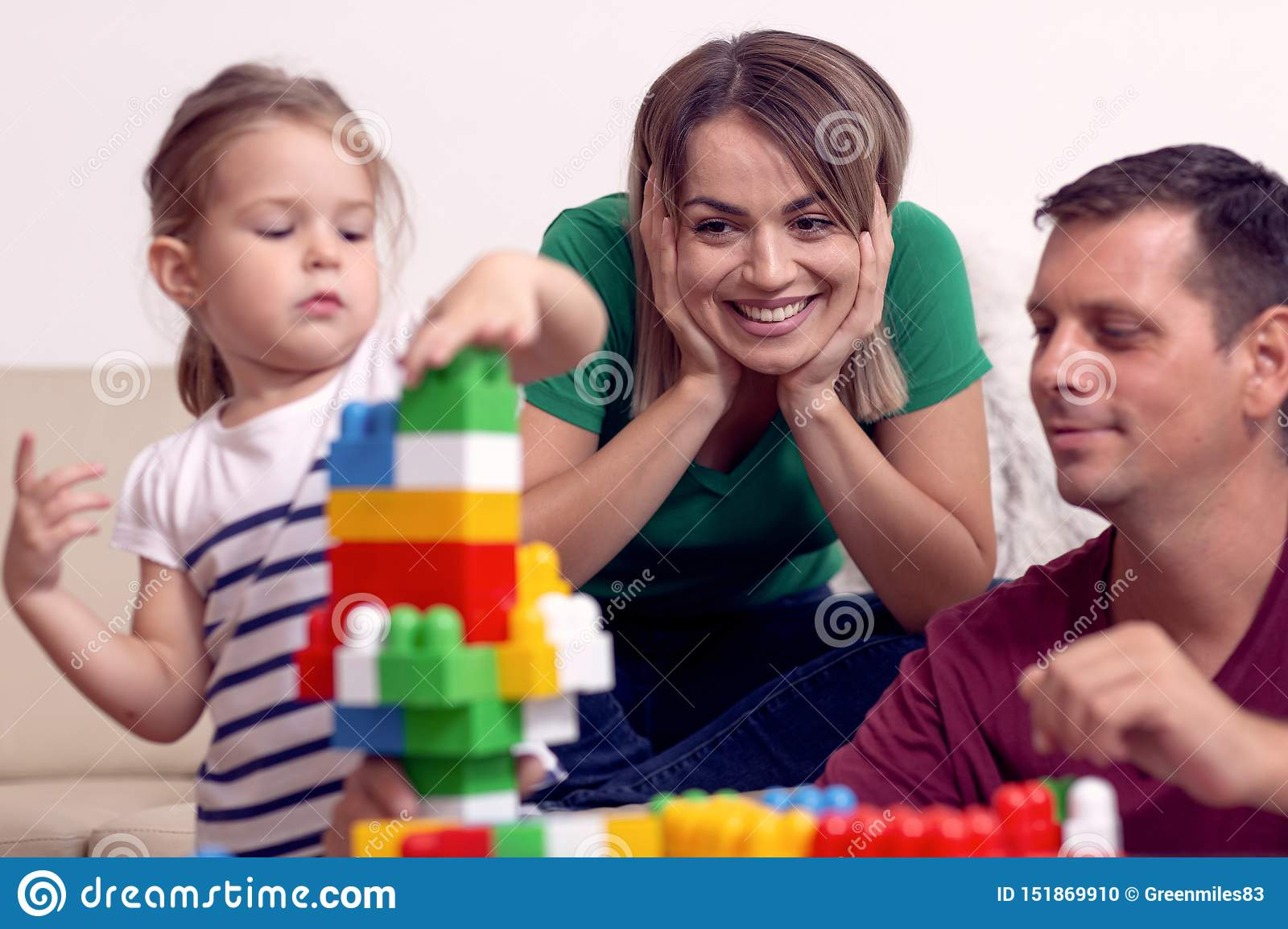 Young family is having fun playing with cute daughter at home