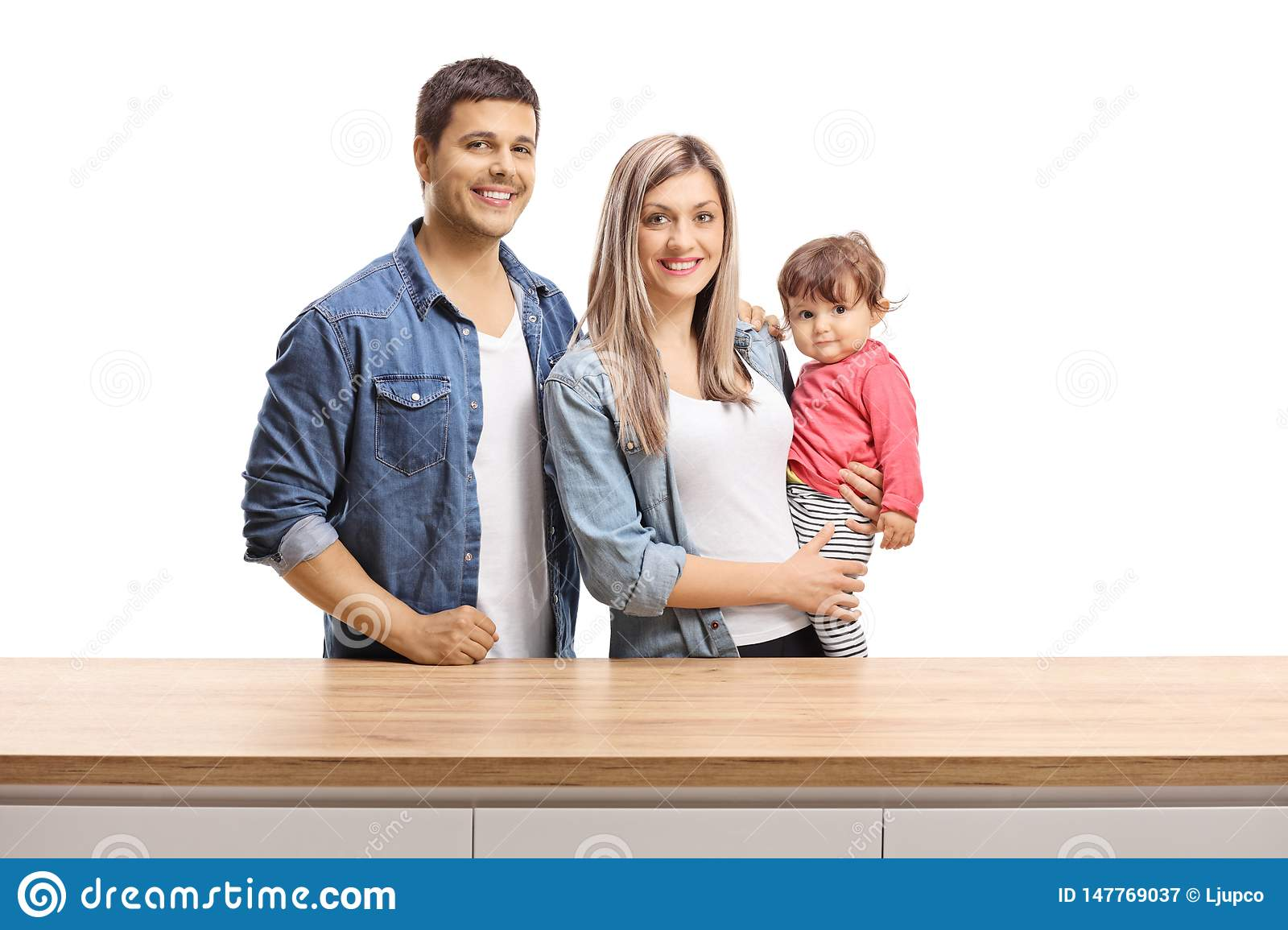 Young family of a mother, father and a baby girl posing behind a wooden counter