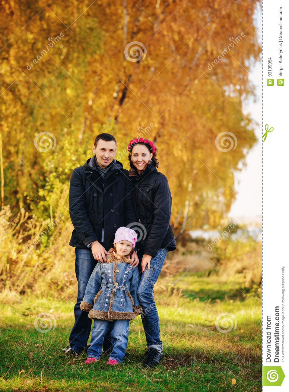 Young family, parents with small children in golden autumn city park
