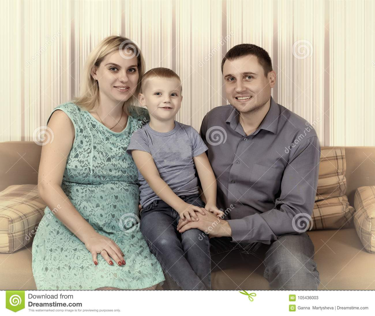 Young family is resting at home on the couch. A pregnant mother, a small son and a father.