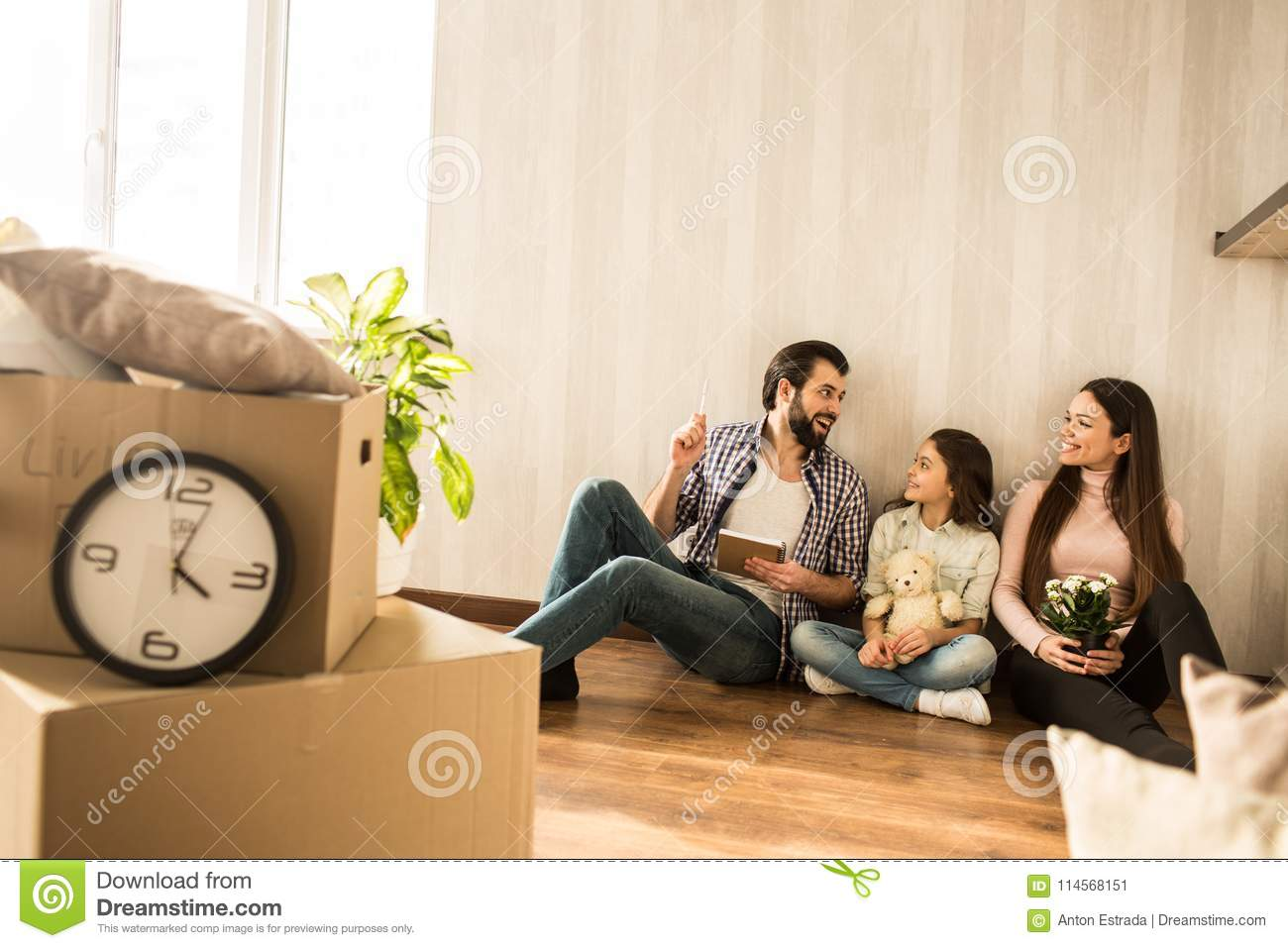 Young family is sitting together on the floor in the living room. They have just moving into this apartment. Girls are