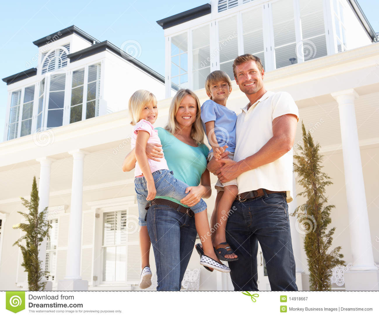 Young Family Standing Outside Dream Home Royalty Free