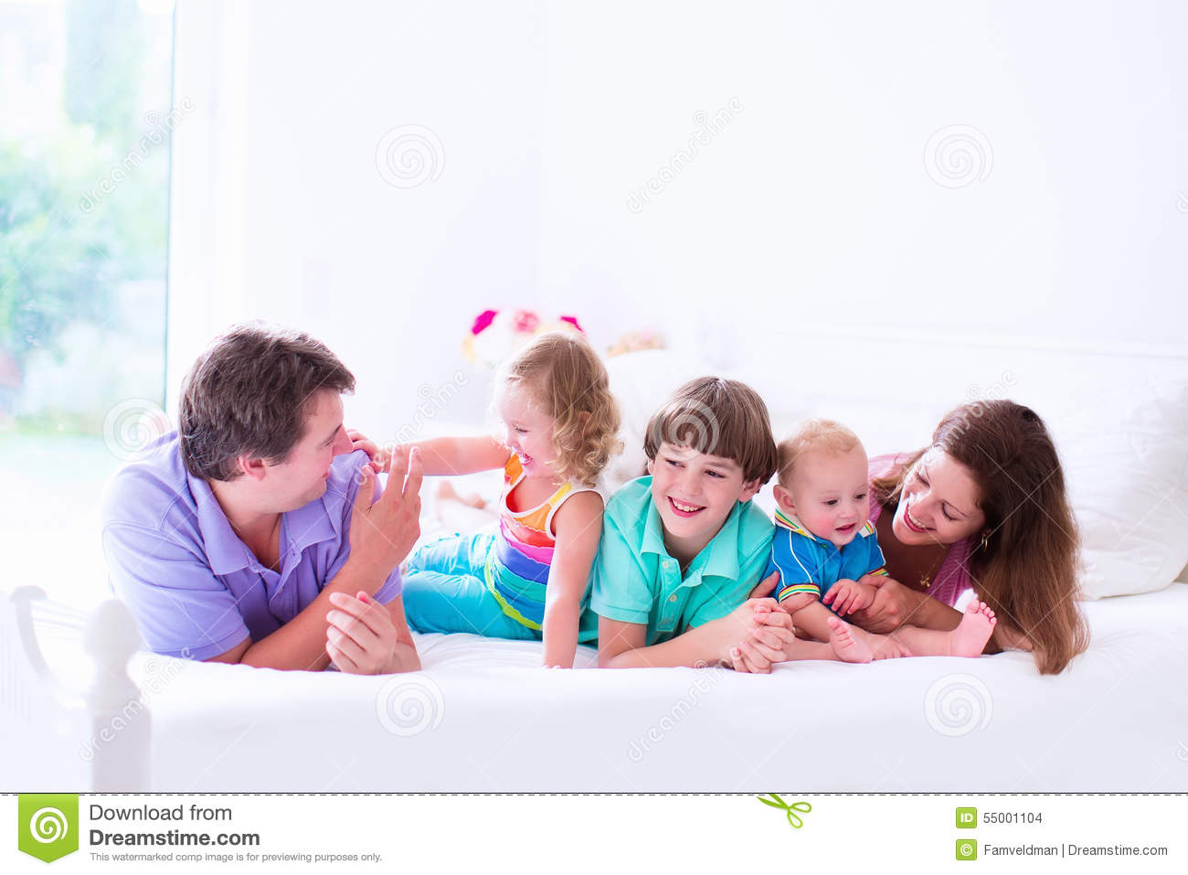 Young Family With Three Kids In Bedroom Stock