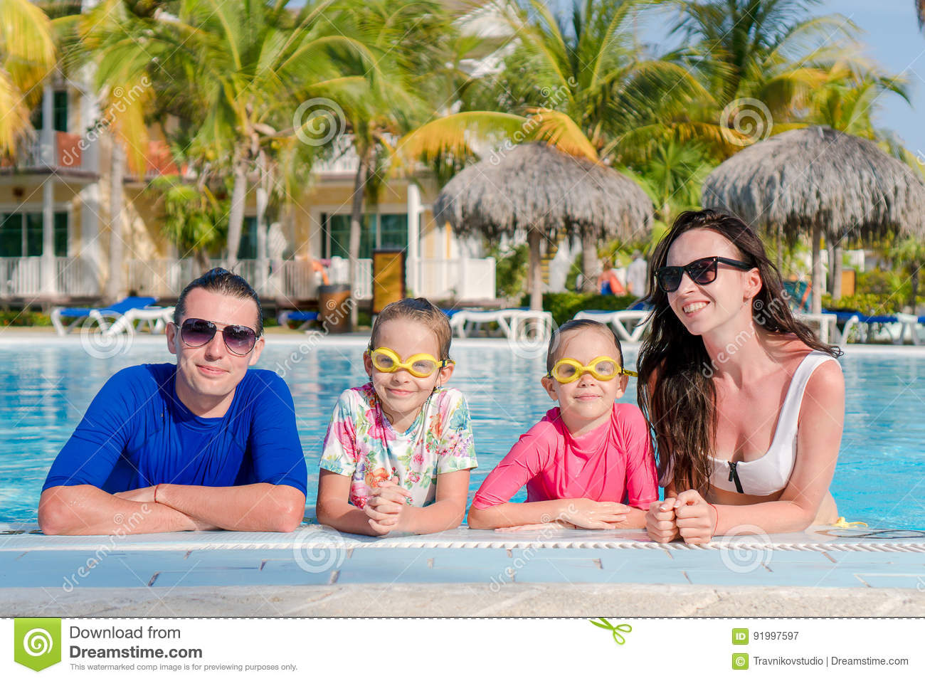 Young family with two kids enjoy summer vacation in outdoor pool