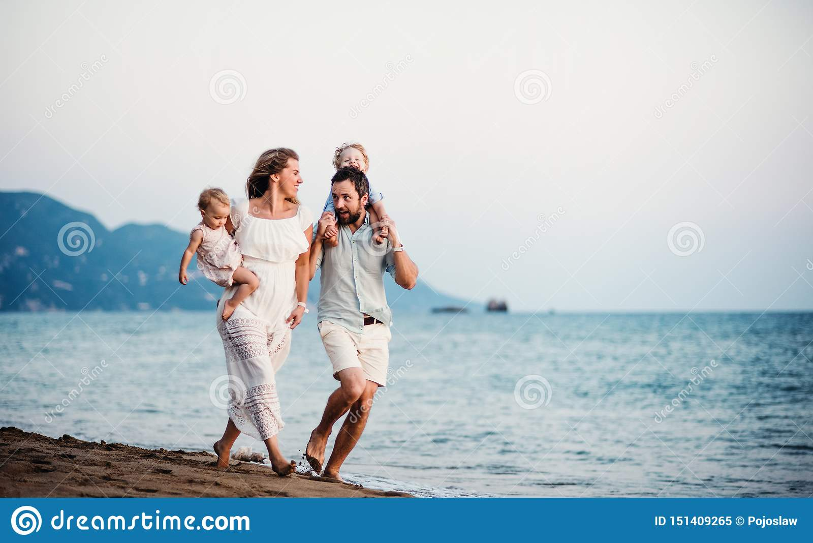 Young family with two toddler children walking on beach on summer holiday.
