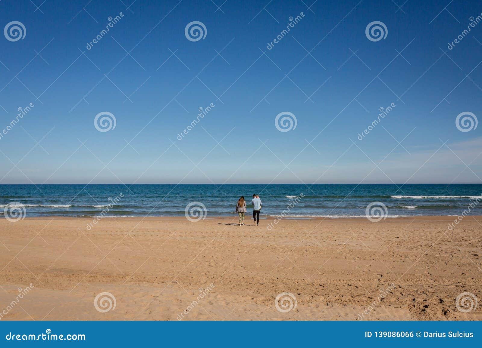 Young family walking in empty beach Gandia, Spain