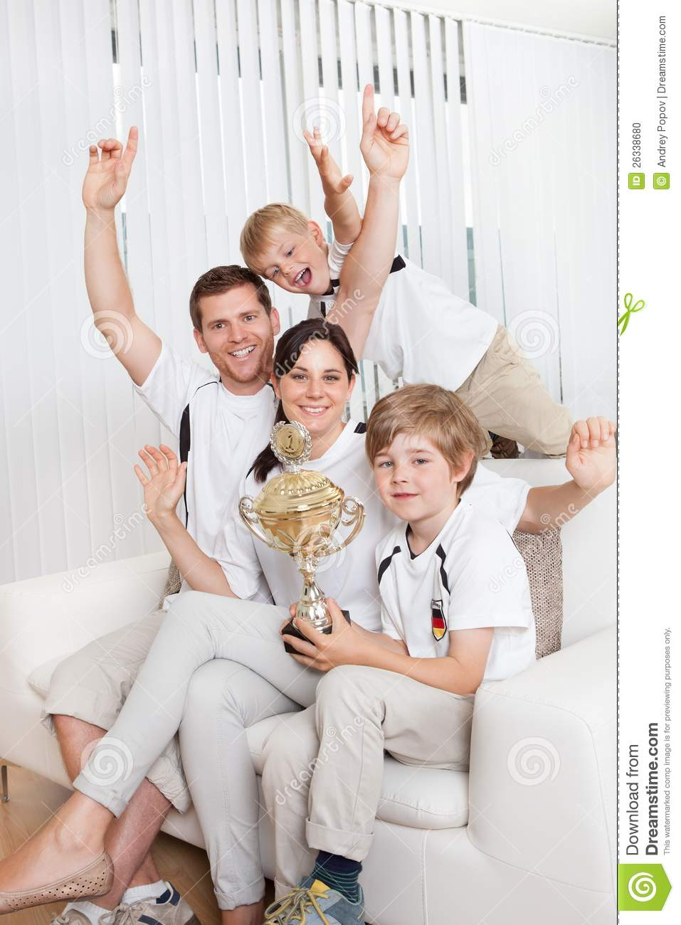 Young family watching football match at home Family Football