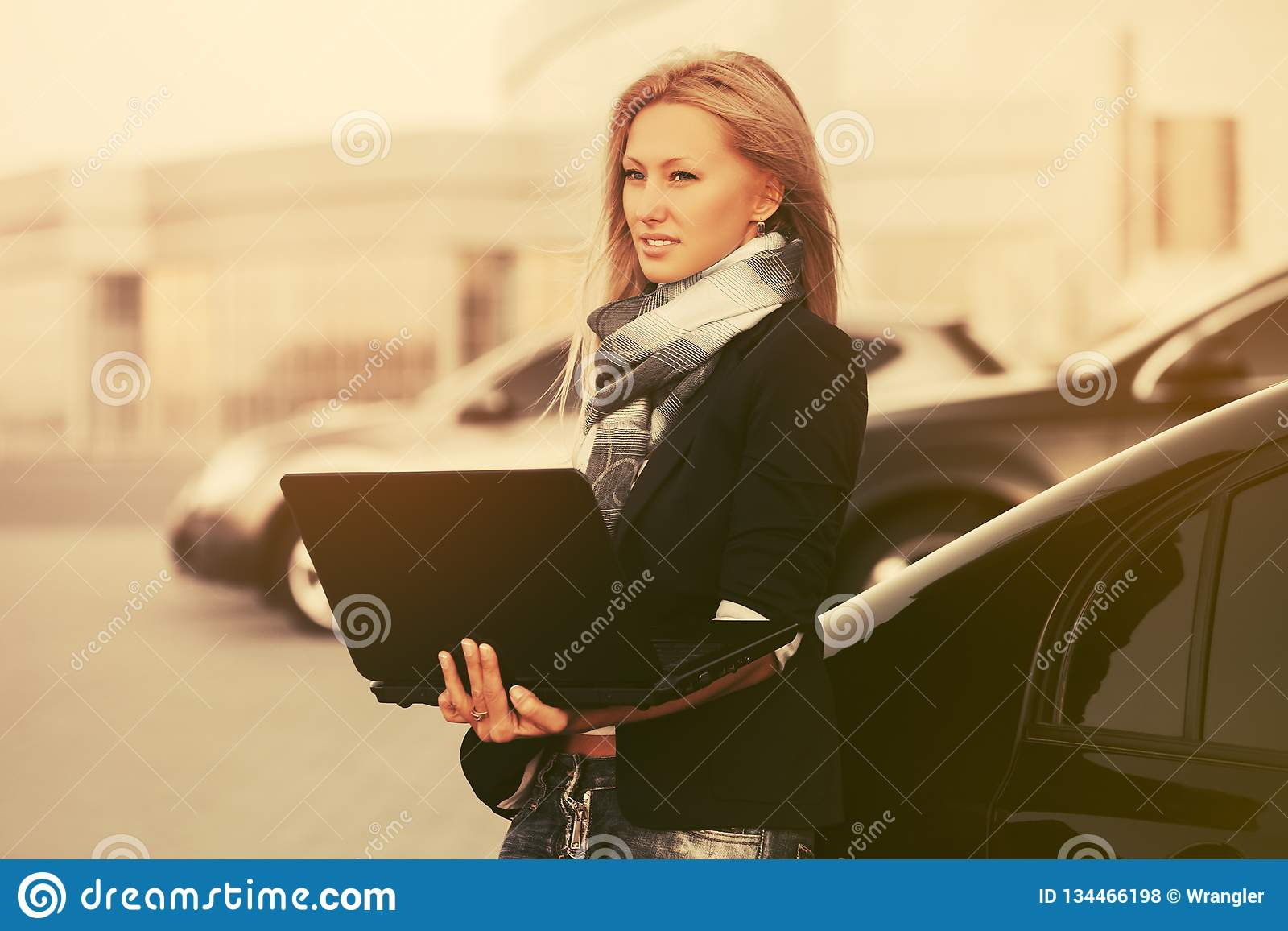 Young fashion business woman with laptop next to her car on parking