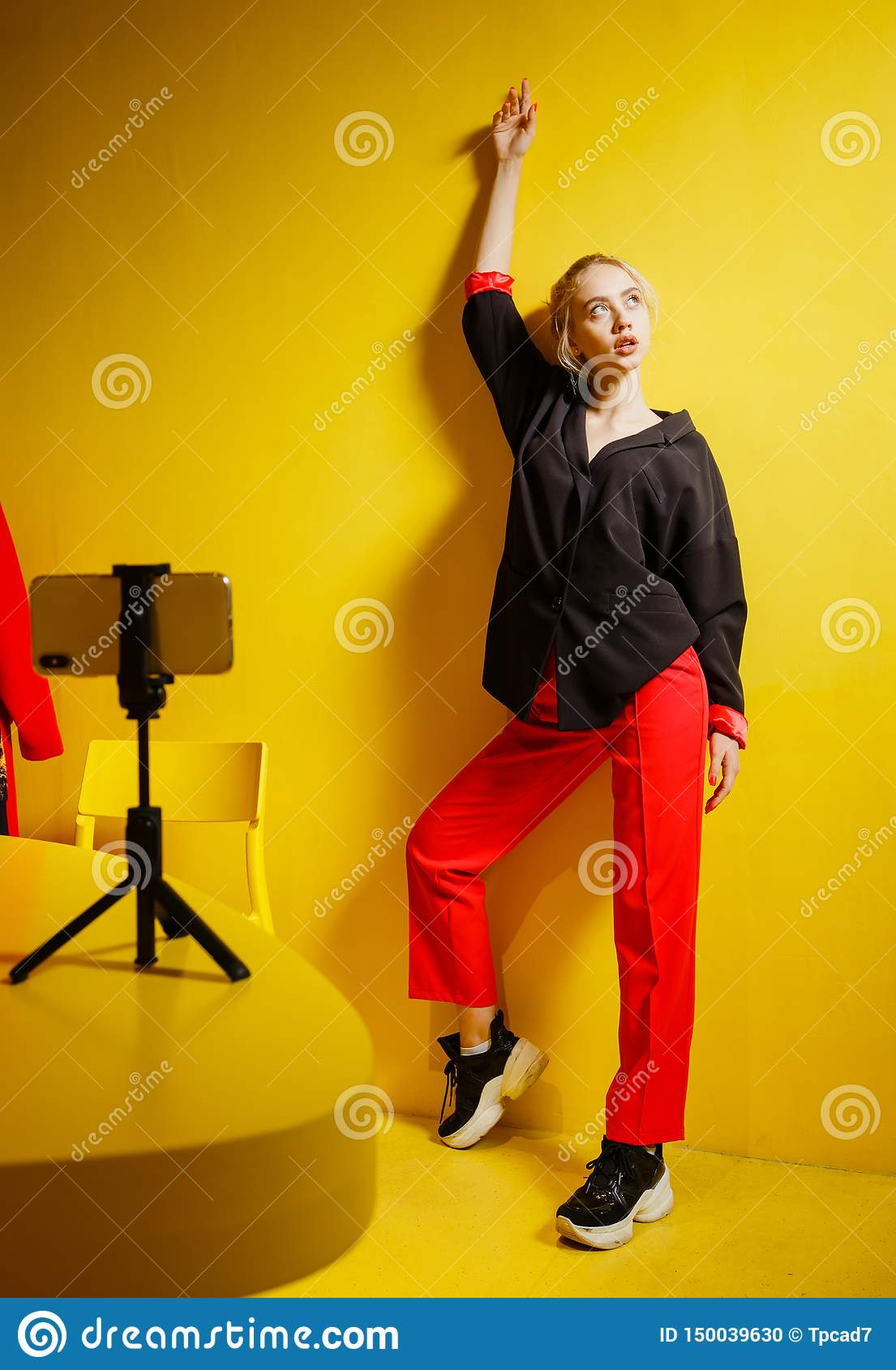 Young fashion girl blogger dressed in red trousers and black jacket takes a selfie on the smartphone standing on a stand