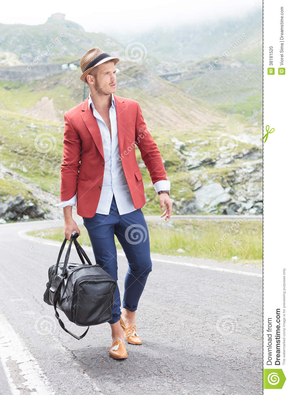 Young fashion man walks on the road