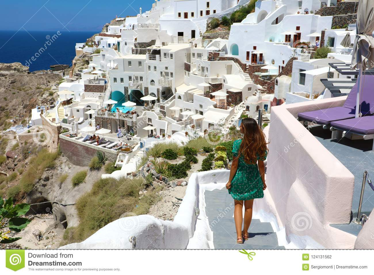 Young fashion woman with green dress and walking on stairs in Oia, Santorini. Female travel tourist on her summer vacations