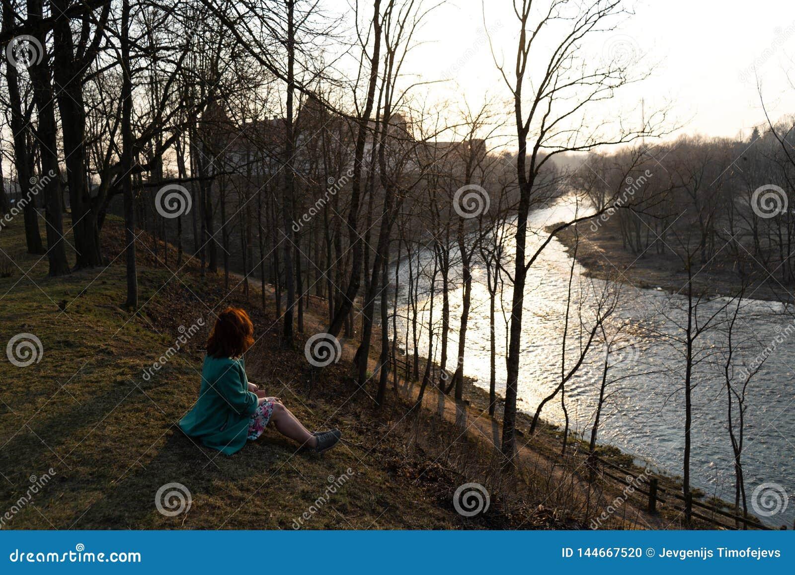 Young fashion woman relaxing and enjoying sunset near a river in Bauska, Latvia, 2019