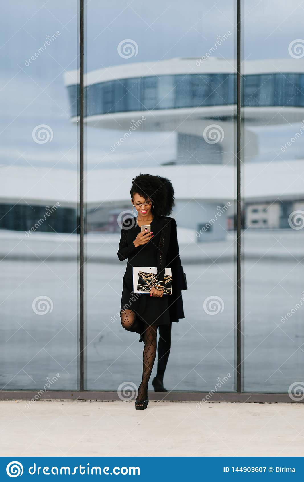 Young fashionable businesswoman using cellphone