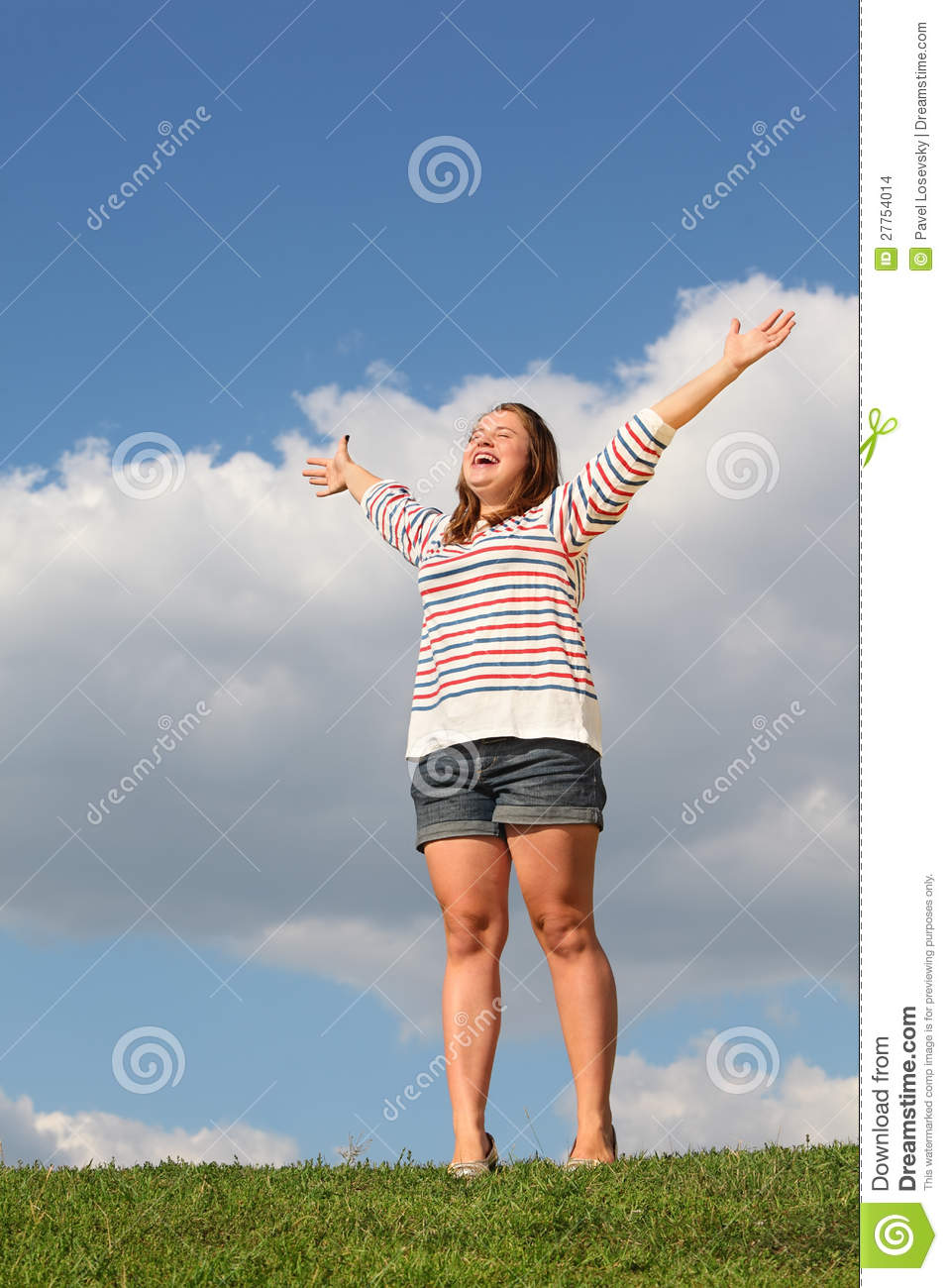 Young fat girl stands at grass, raises her hands