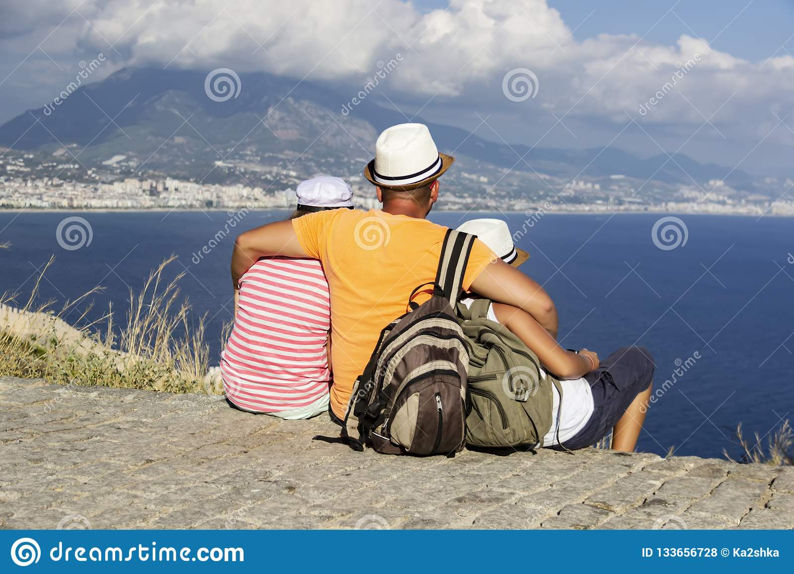 Young father, daughter and son with backpacks are sitting on the beach against the backdrop of the sea. Family travel concept