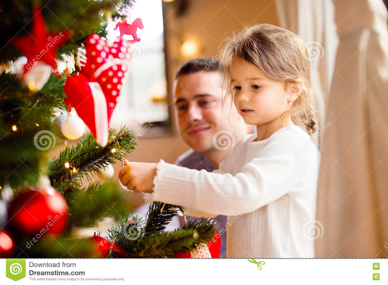 Young father with daugter decorating Christmas tree together.