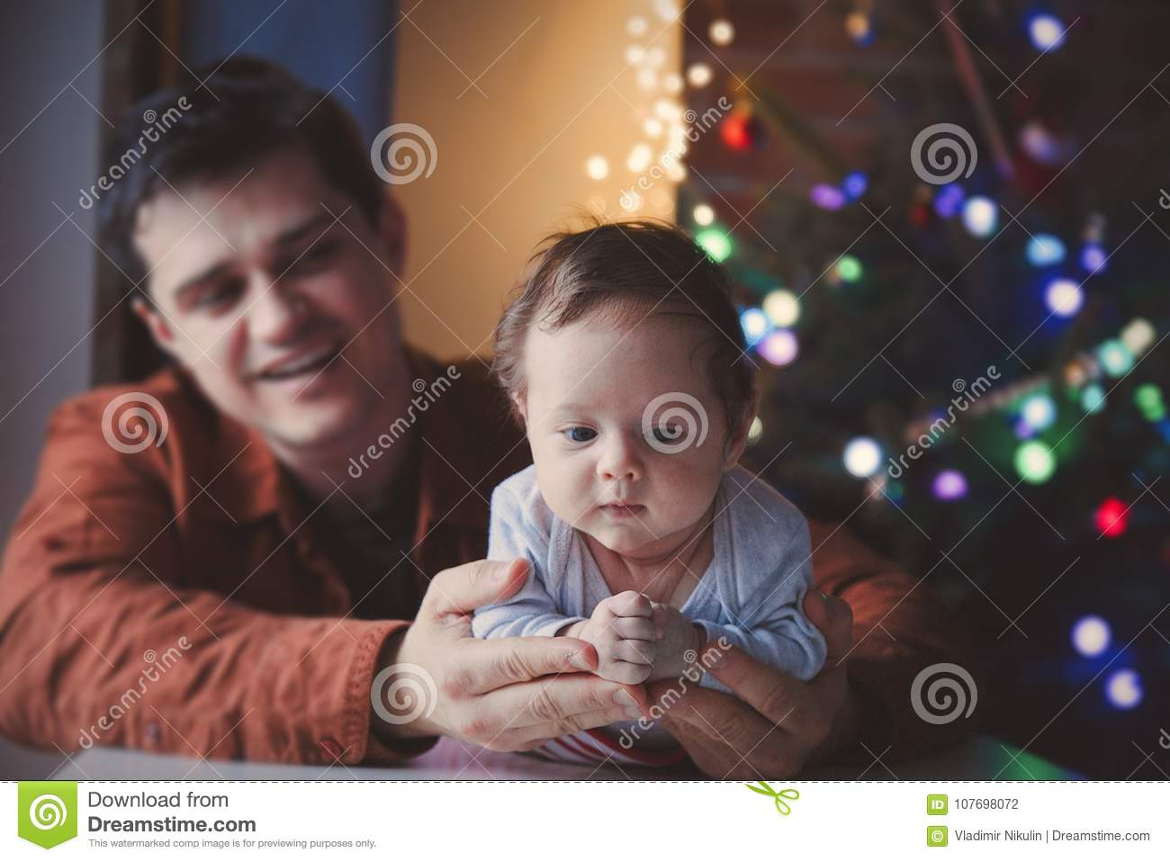 Young father help to a little child lie down on tummy