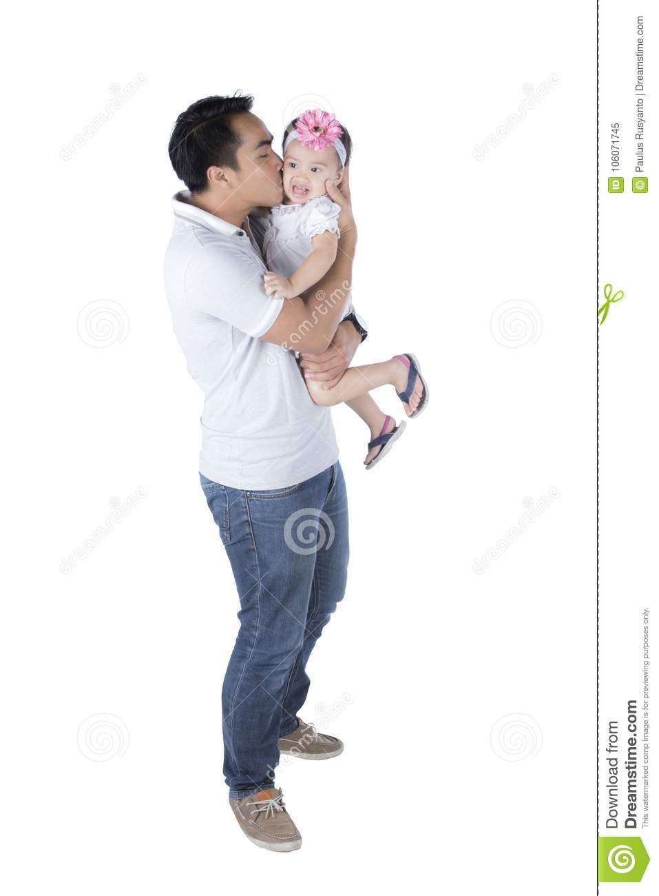 Young father kissing his daughter on studio