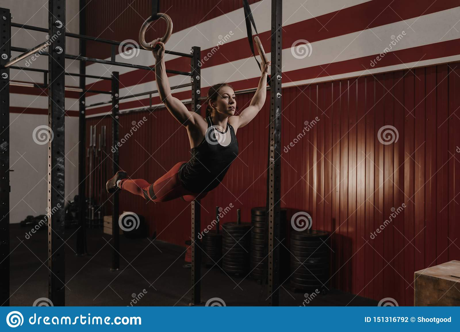 Young female athlete swinging on gymnastic rings at crossfit gym