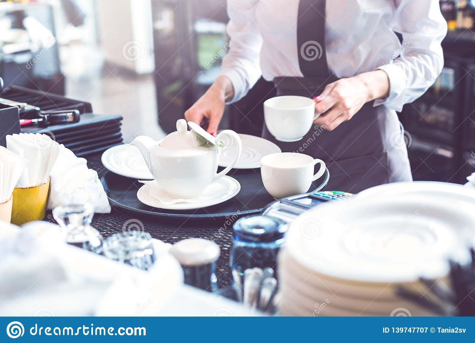 Young female barista serving tea to customers in cafe