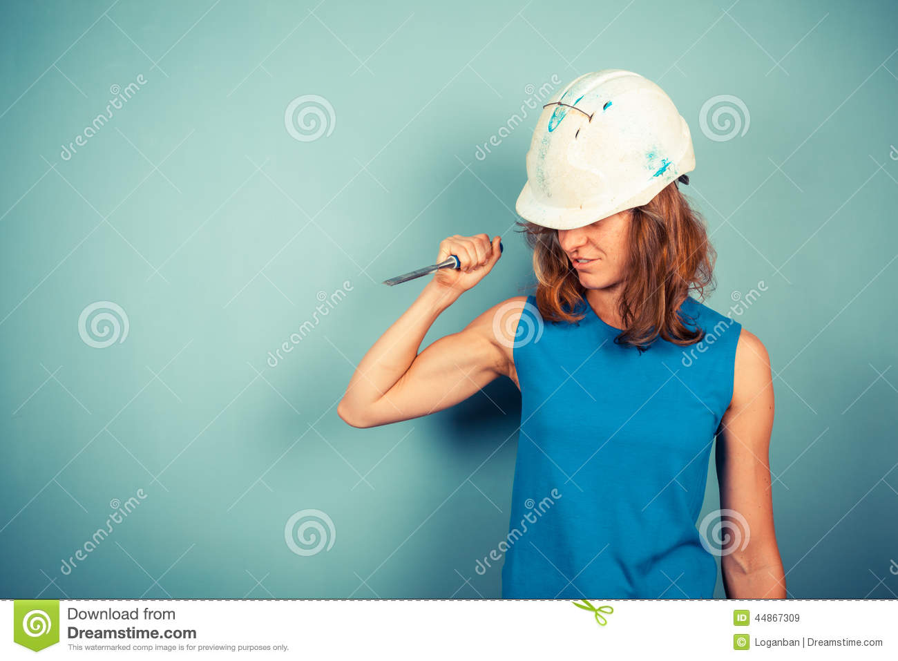 Young female builder holding a chisel aggresively