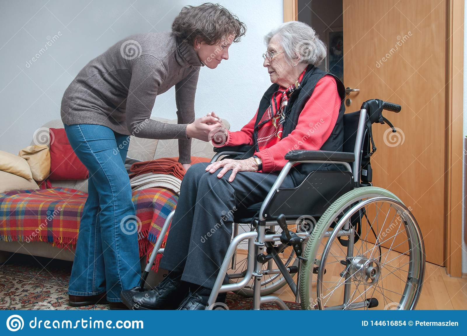 Young woman holding hand of sad senior woman with wheelchair