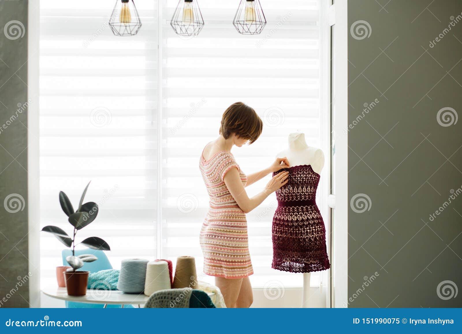 Young female clothing designer using dress dummy at cozy home interior, freelance lifestyle