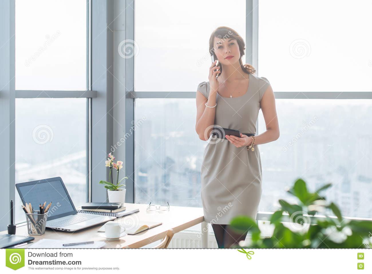 Young female consultant having business call in office at her workplace. Secretary speaking on the smart phone, holding