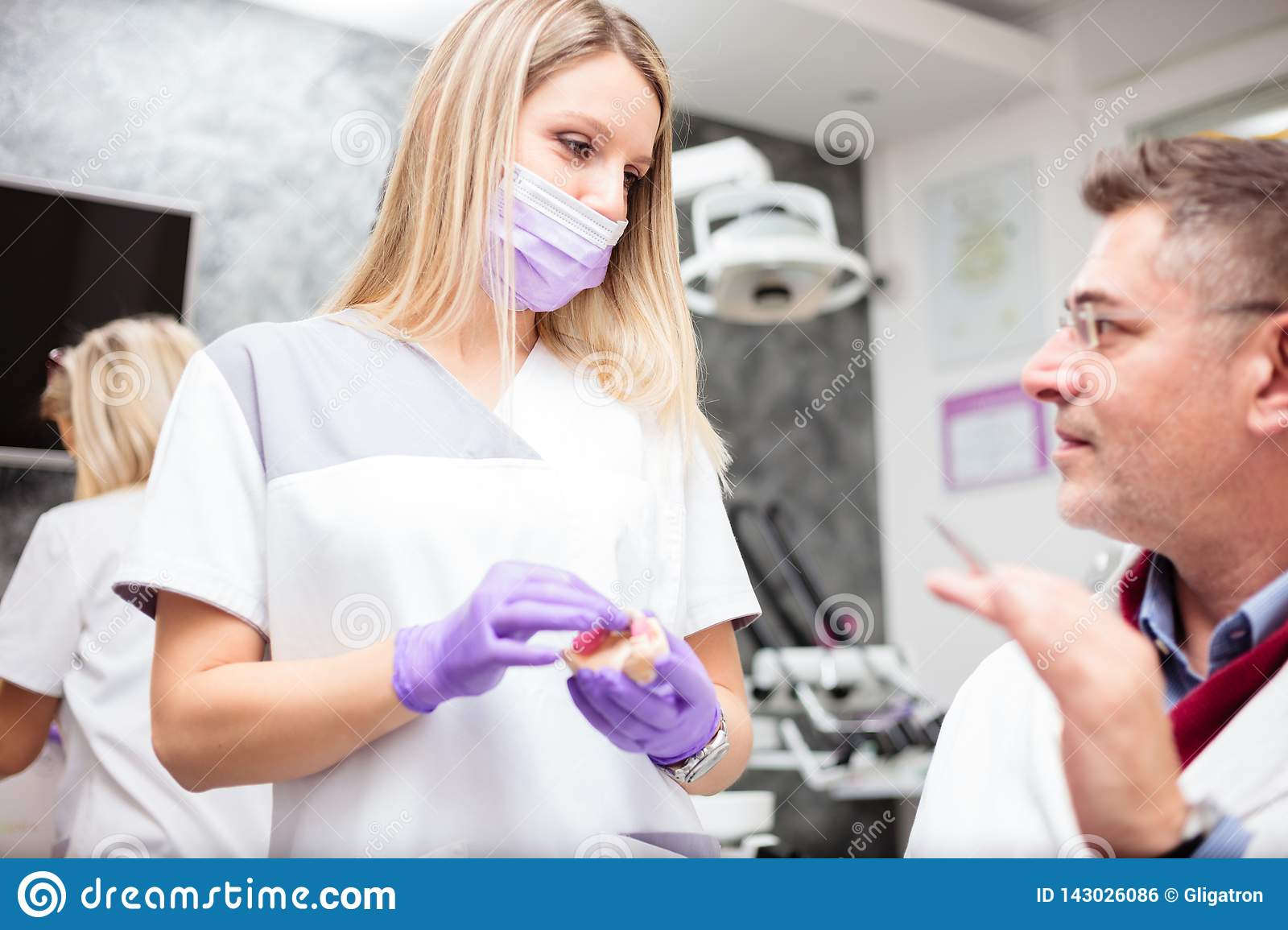 Young female dental technician consulting with a mature male doctor in dental clinic