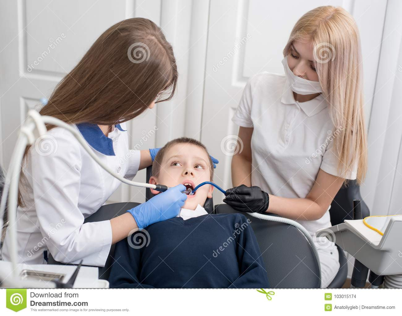 Young female dentists examining and working on boy patient