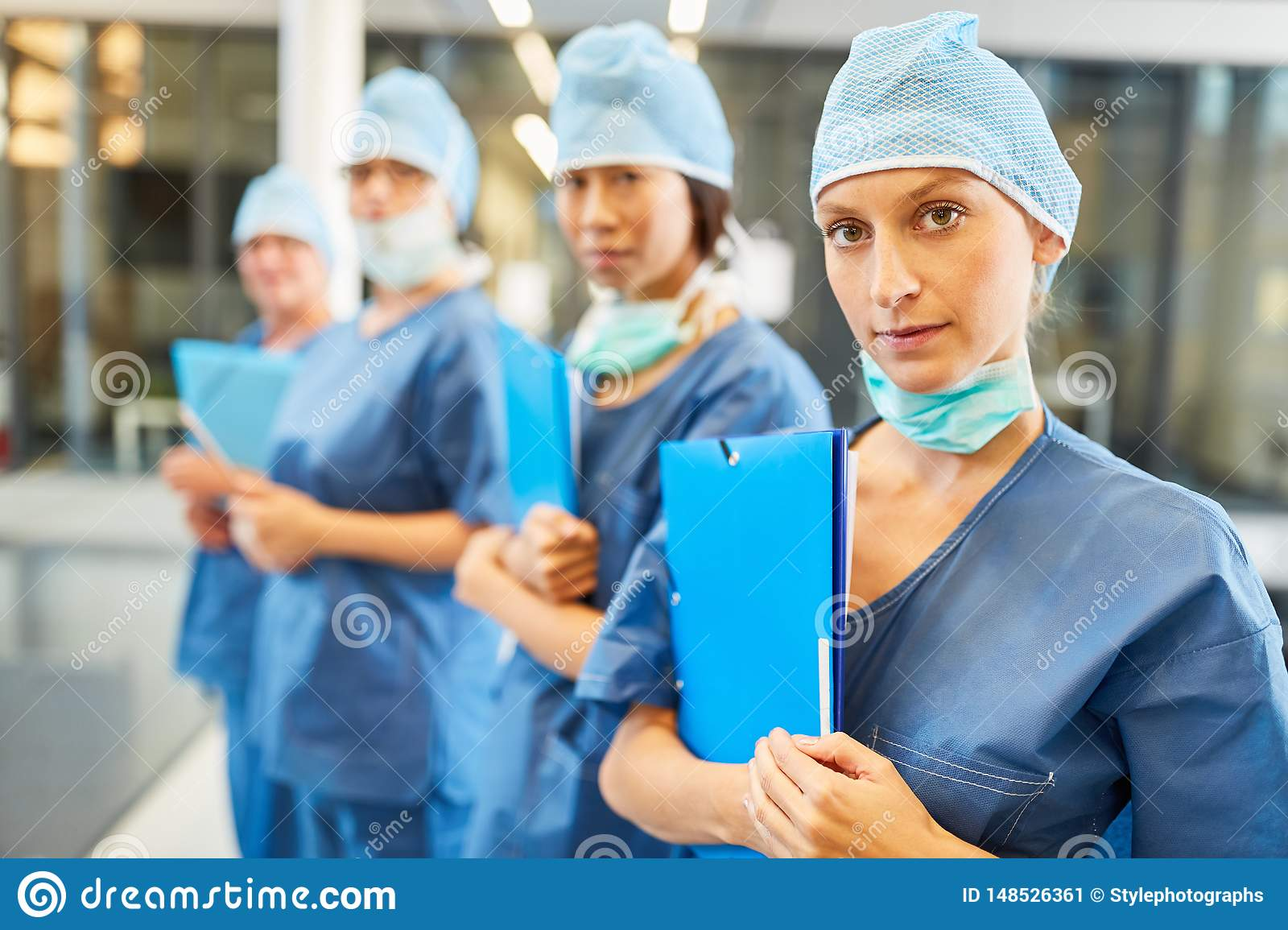 Young female doctor in blue surgical clothing with her team