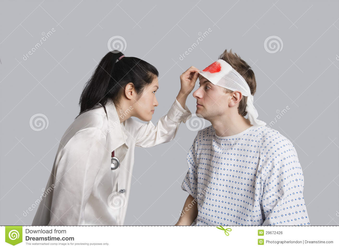 ... Stock Image: Young female doctor examining an injured male patient