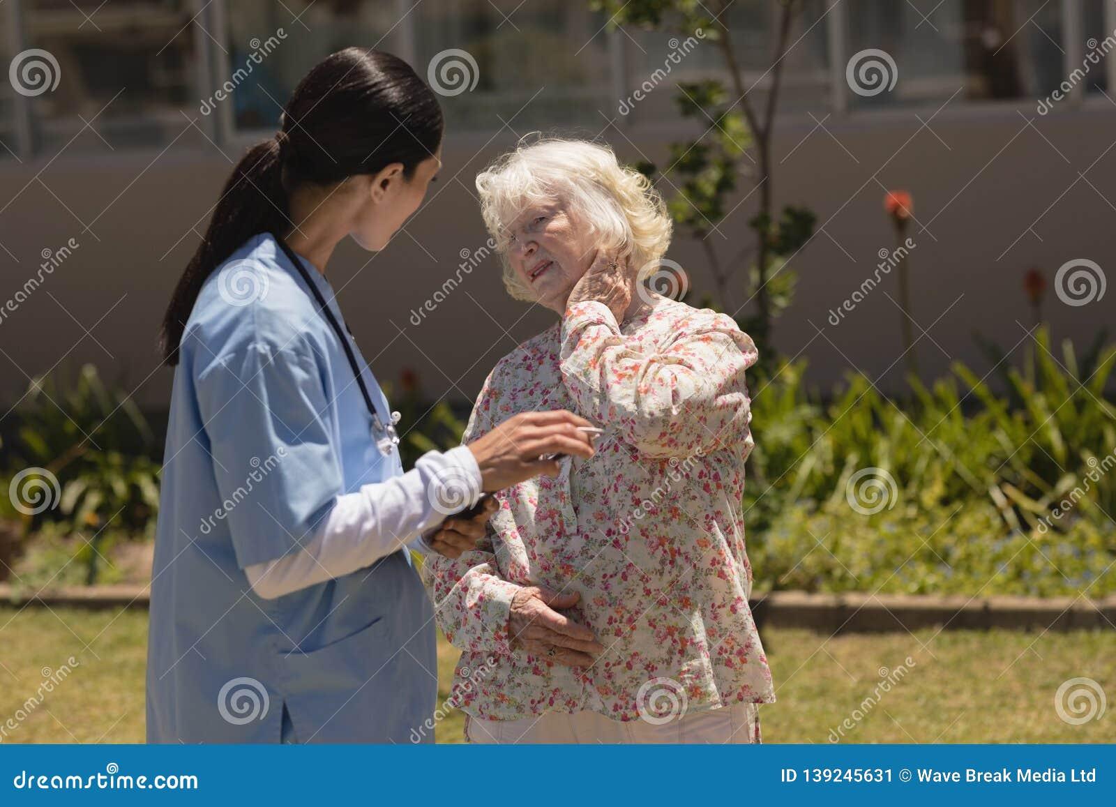 young female doctor examining senior woman in garden