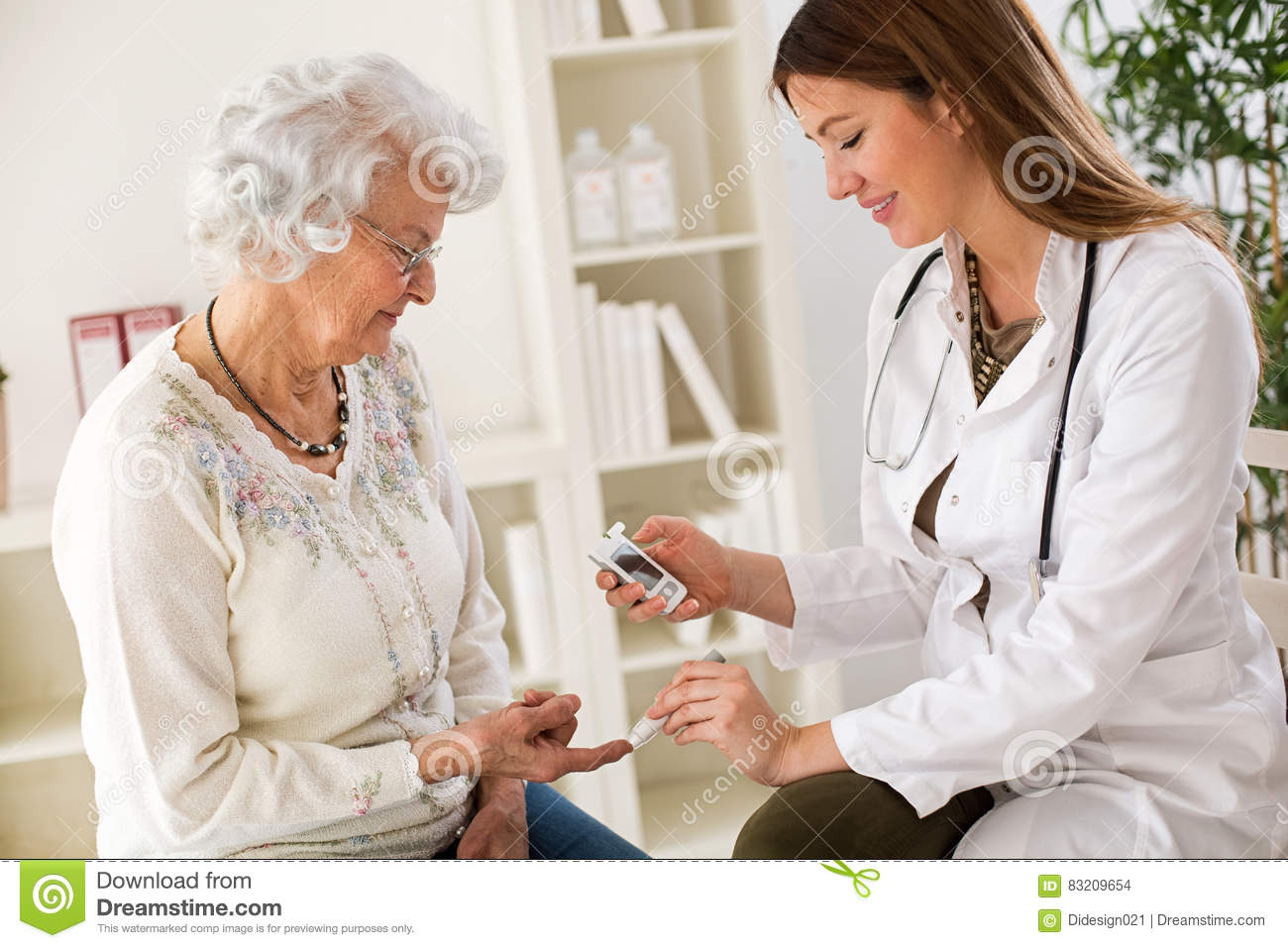 Young female doctor making diabetes blood test on senior woman