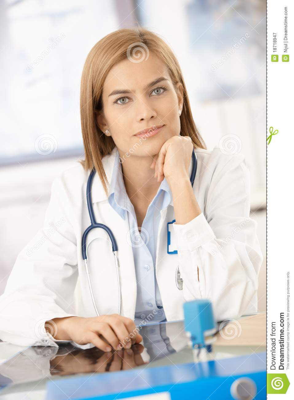 Young Female Doctor Sitting At Desk In Office Royalty Free Stock